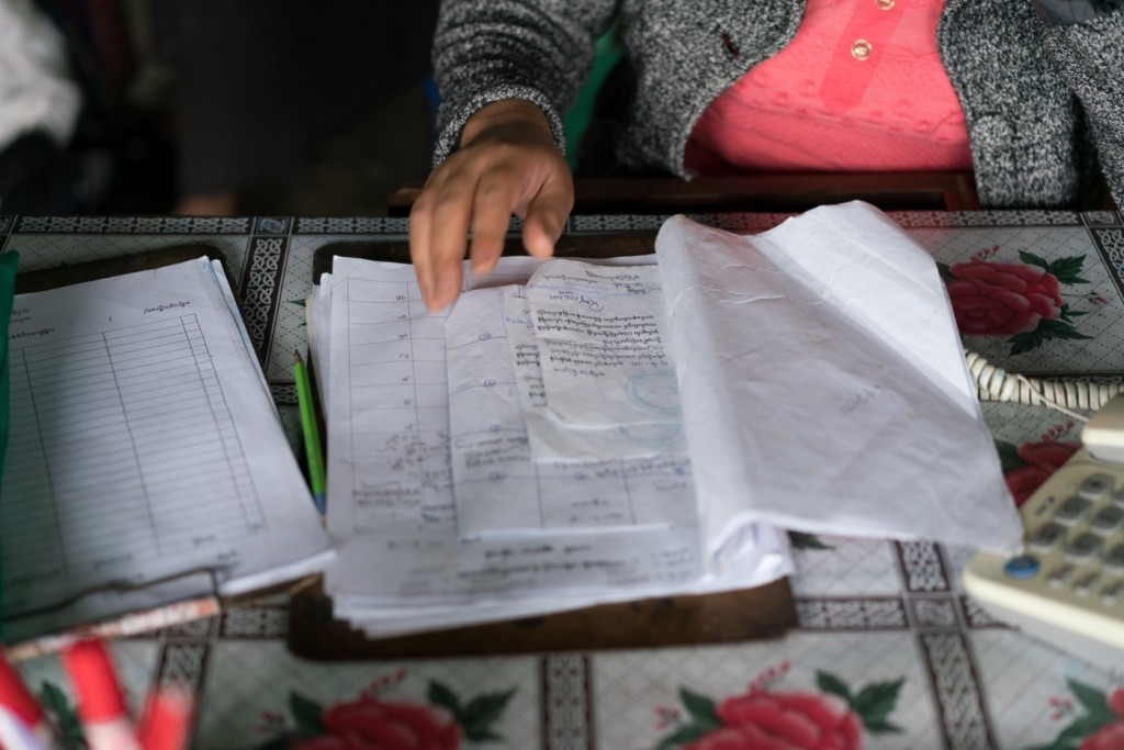 مشارك في البحث يعرض مستندات هوية أسرته. ملكية الصورة: كريس مارمو |Paper Giant